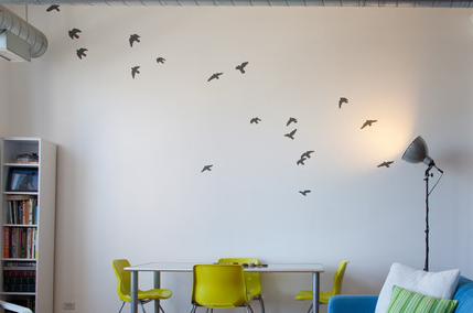 Painting of a flock of birds on a living room wall in a loft.