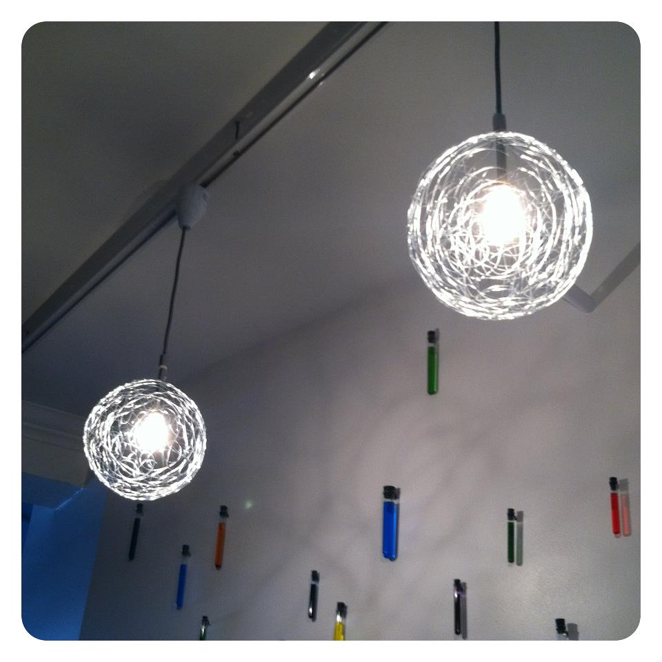 Galvanized wire pendant lights with test tubes decorating a wall