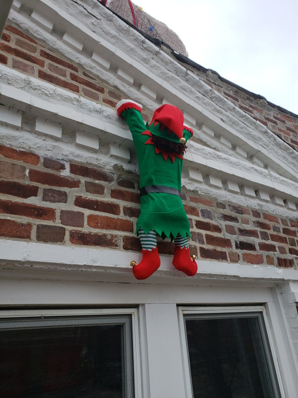 After dressing the elf - felt, bells, yarn hair and lots of hot glue - screws were placed in the hands. He was secured to the façade with small nails and wire.
